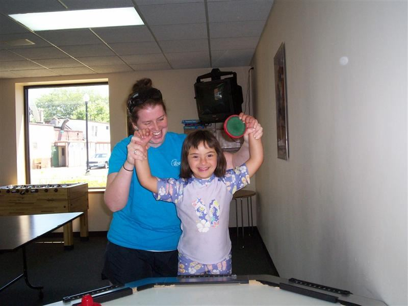 A woman playing air hockey with a young girl.