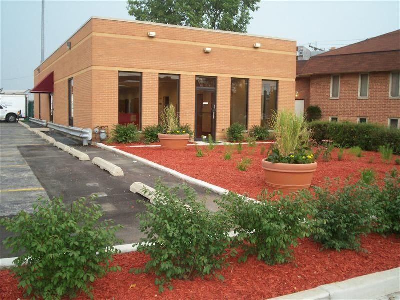 A clean brick building with a garden out front.