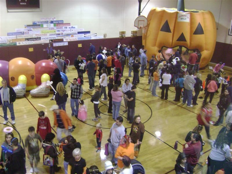A crowed gymnasium with an inflatable pumpkin in the corner.
