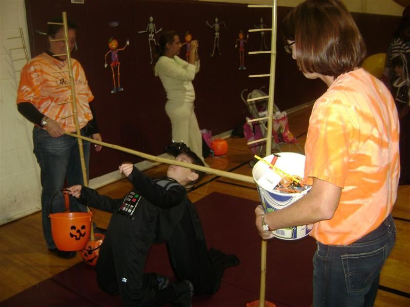 A girl in a witch costume doing limbo.
