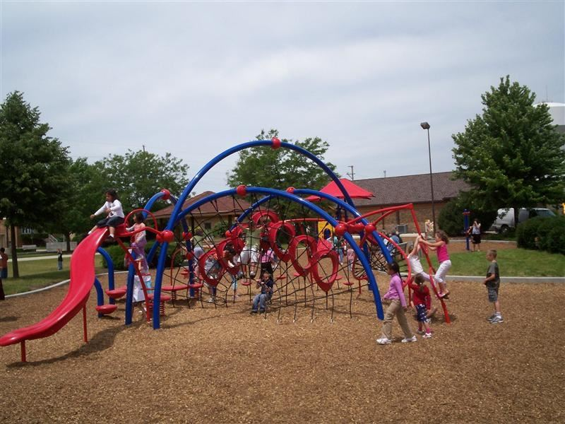 Children playing on red and blue play equipment.