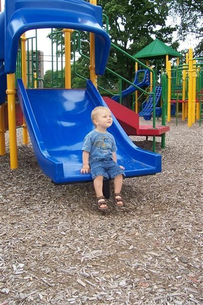 A young boy on a blue slide.