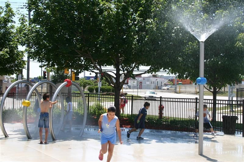 Children playing in water sprinklers.