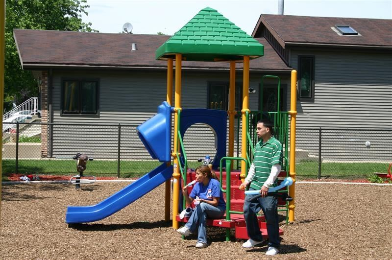 People sitting on a bench near play equipment.