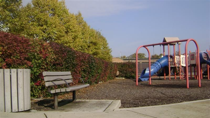 A bench next to blue, red, and brown play equipment.