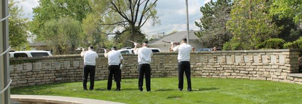 Four men pointing ceremonial rifles into the air.