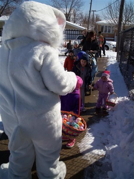 A person in an Easter bunny costume speaking to children.